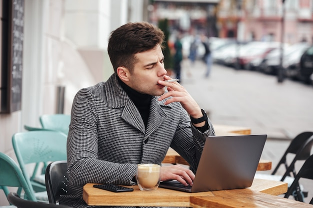 Photo of handsome man in gray coat smoking cigarette, and drinking cappuccino while resting in cafe outdoors Free Photo