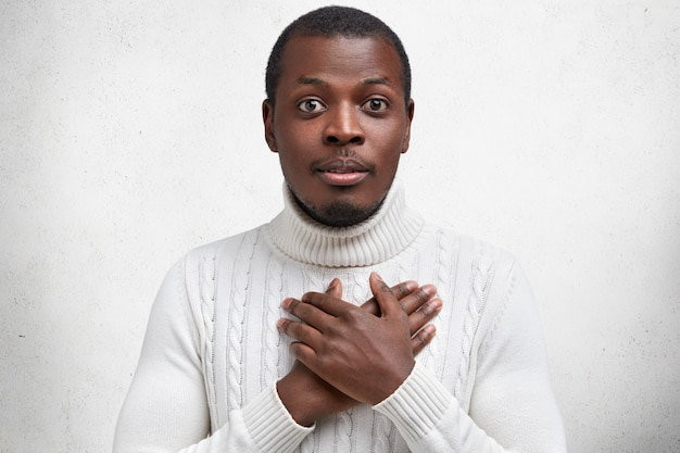 Photo of handsome young dark skinned male holds hands on chest as expresses gratitude, being pleased with heart piercing story Free Photo