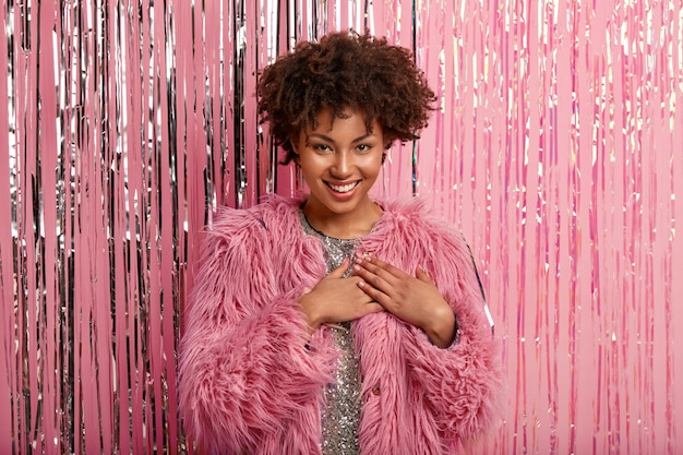 Photo of happy dark skinned afro woman keeps both palms on chest, expresses gratitude, wears sparkling dress and pink coat Free Photo