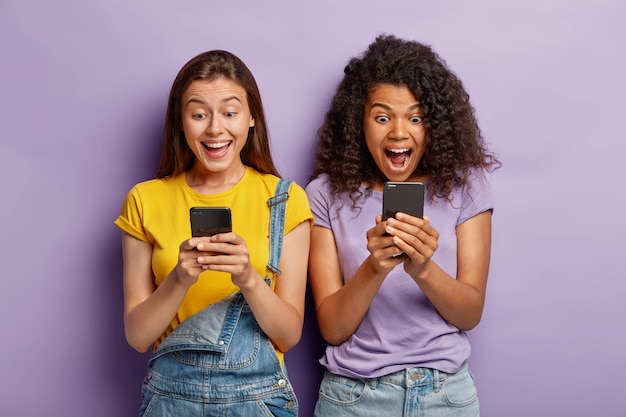 Photo of happy diverse female friends ignore live communication, chat in web blog via cell phones, gaze with positive expressions at screens Free Photo