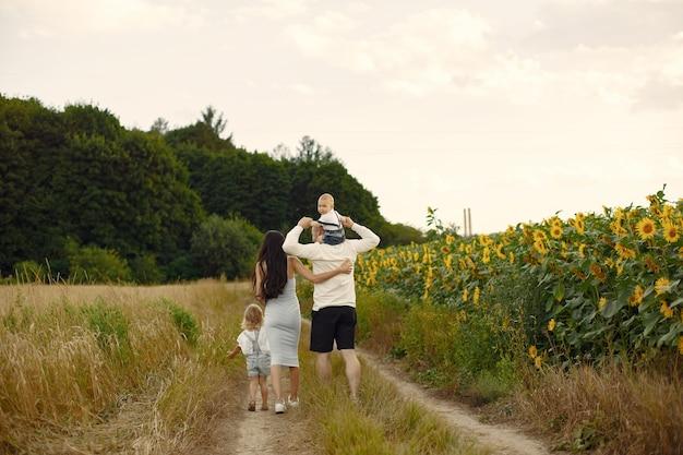 Foto di famiglia felice. genitori e figlia. famiglia insieme nel campo di girasoli. uomo in camicia bianca. Foto Gratuite