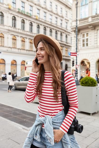 Foto di felice giovane turista femminile in abito elegante, passeggiate in città, ha tour, porta la fotocamera sulla spalla Foto Gratuite