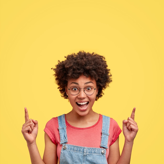 Foto di una gioiosa femmina afroamericana con un sorriso positivo, capelli crespi, punta sopra con le dita indice, ha un'espressione felice, posa contro il muro giallo. felice donna dalla pelle scura al coperto Foto Gratuite