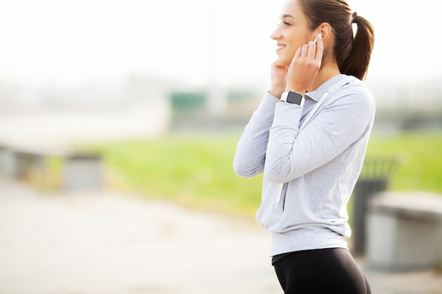 Photo of joyful fitness woman 30s in sportswear touching bluetooth earpod and holding mobile phone, while resting in green park Premium Photo