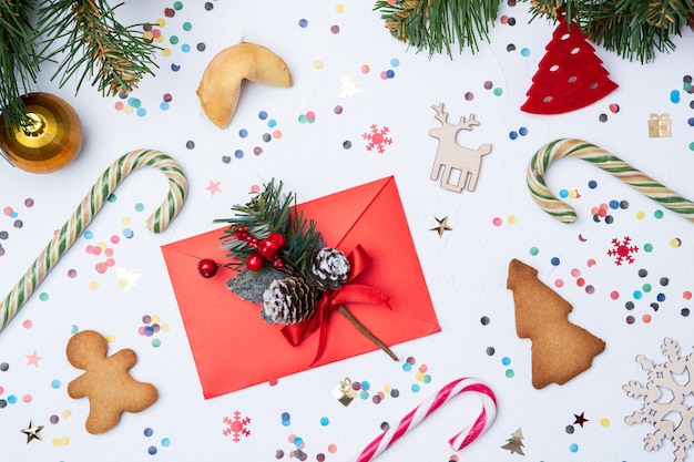 Photo of letter, christmas fir, candy, cookies on white table Premium Photo