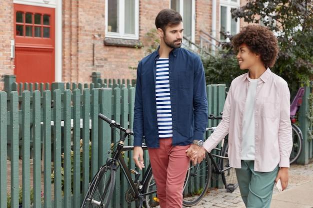 La foto di una bella coppia interrazziale fa una passeggiata all'aperto, tiene le mani unite e si guarda con amore Foto Gratuite