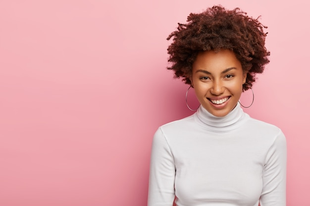 Photo of lovely young lady has curly afro hair, smiles gently, wears earrings and white jumper, being satisfied with getting new job position, has pleasant talk with colleague, stands over pink wall Free Photo