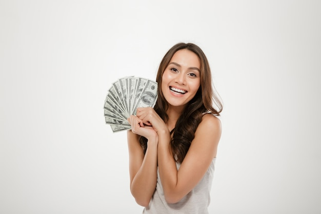 Photo of lucky smiling woman with long hair winning lots of money dollar bills, being rich and happy over white wall Free Photo