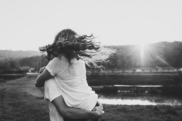 Photo married couple hugging, husband and wife near lake. close up. summer. portrait of a romantic young man and woman in love in nature. husband and wife on sunlight. black and white photo. Premium Photo