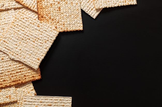 A photo of matzah or matza pieces  on black. matzah for the jewish passover holidays. place for text, copy space Premium Photo