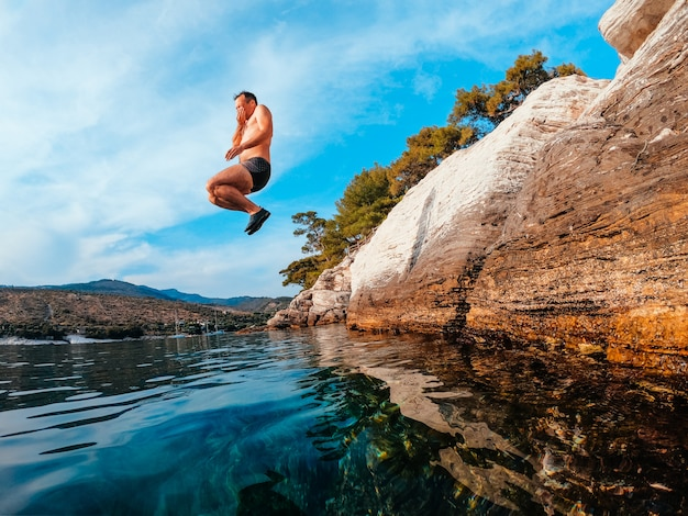 Photo of men in mid air jumping into water Premium Photo