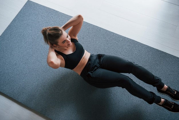 Photo in motion. doing abs on the floor in the gym. beautiful female fitness woman Free Photo