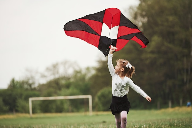 Photo in motion. happy girl in casual clothes running with kite in the field. beautiful nature Premium Photo