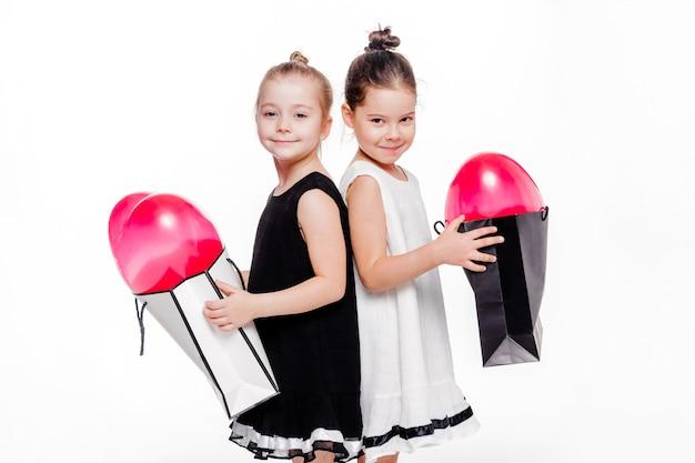 우아한 드레스를 입은 2 명의 어린 소녀 사진이 안에 하트 모양의 풍선이있는 큰 가방을 들고 있습니다. 프리미엄 사진