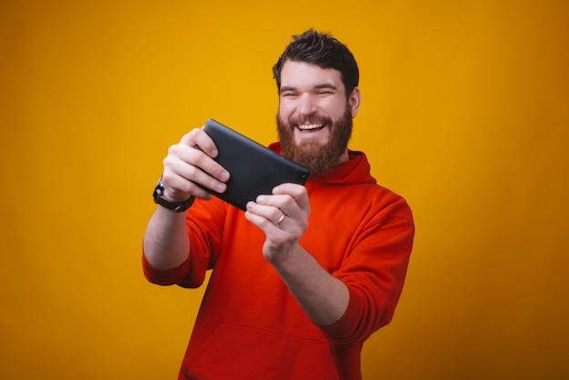 陽気な若い男の写真は、黄色のスペースで彼のタブレットでゲームをプレイすることに興奮しています。 Premium写真