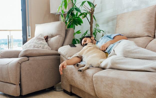彼の犬と一緒にソファで寝ているハンサムなヒスパニック系男性の写真 無料写真