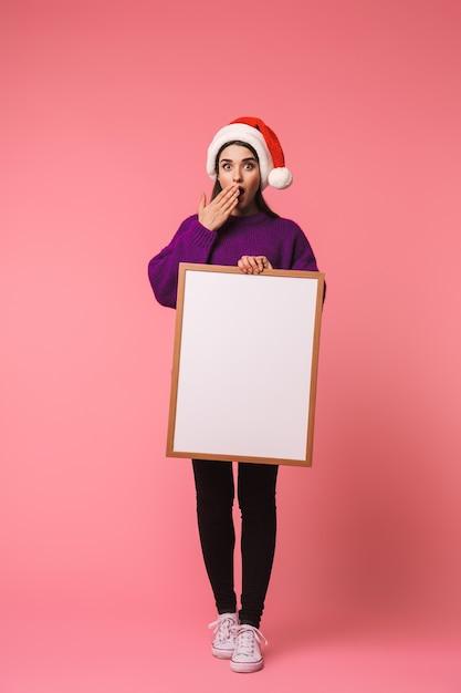 핑크 Copyspace 빈 들고 이상 격리 포즈 충격 된 행복 젊은 감정적 인 여자의 사진. 프리미엄 사진
