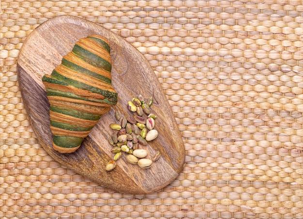 Фотография традиционного свежеиспеченного круассана с аппетитным фисташковым кремом. Premium Фотографии