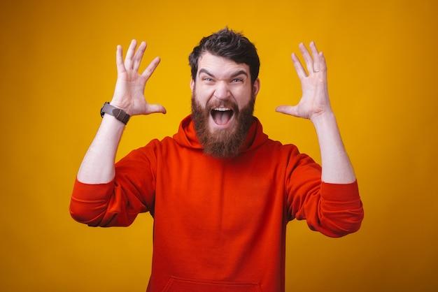 あごひげを生やした若いひげを生やした男の写真は、黄色の空間でカメラに向かって叫んでいます。 Premium写真