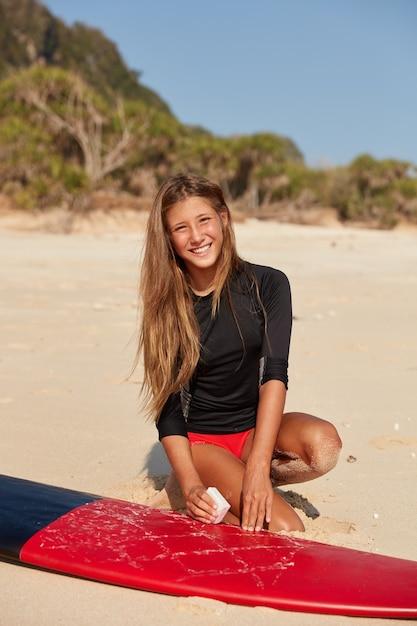 水着を着たアクティブな女性サーファーの写真、長い髪、心地よい笑顔、セッション前に表面にワックスをかけてサーフボードを準備する 無料写真