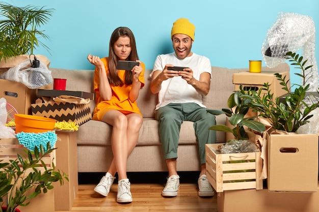 中毒の千年紀の男と女がスマートフォンでオンラインゲームをプレイする写真 無料写真