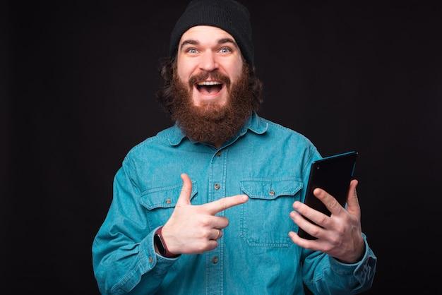 Фотография изумленного бородатого хипстера, указывающего на планшет Premium Фотографии
