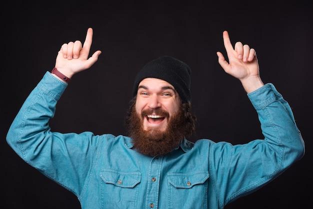 Фотография изумленного бородатого мужчины в синей рубашке, указывающего вверх на черном фоне Premium Фотографии