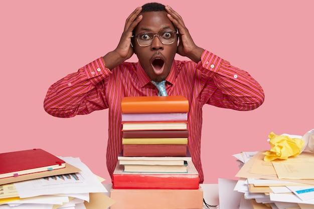 驚いた黒人男性の写真は頭を抱え、圧倒的な表情で見つめ、試験のためにすべての本を読まなければならず、年次報告書を作成します 無料写真