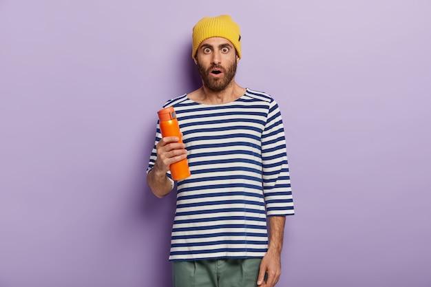 驚いた無精ひげを生やした若い男の写真はスタイリッシュな黄色の帽子、ストライプのジャンパーを着ています 無料写真