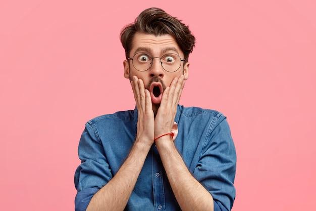 Фотография изумленного бородатого мужчины со стильной стрижкой держит руки на обеих щеках, выглядит удивительно и шокировано, широко открывает рот, одет в джинсовую рубашку, позирует на фоне розовой стены. Бесплатные Фотографии