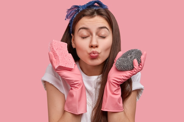 Фотография привлекательной женщины со здоровой кожей, сложенными губами, закрывает глаза, хочет кого-то поцеловать, носит две губки для мытья посуды, носит резиновые розовые перчатки. Бесплатные Фотографии