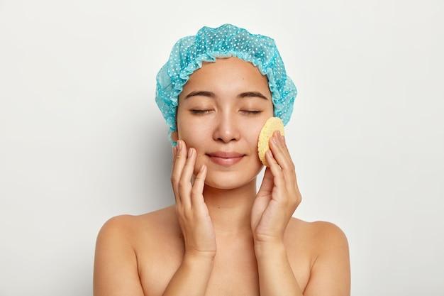 매력적인 아시아 여성의 사진은 화장품 스폰지로 얼굴을 씻고, 얼굴을 정화하고, 토플리스를 서며, 눈을 감고, 파란색 Bathcap을 착용합니다. 무료 사진