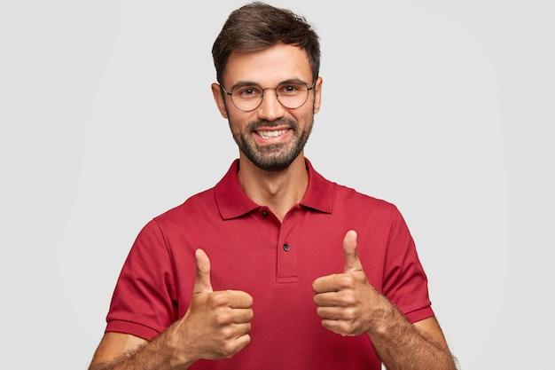 魅力的なひげを生やした若い男の写真は、両手で大丈夫なジェスチャーをし、何かが好きで、赤いカジュアルなtシャツを着て、白い壁にポーズをとって、屋内でジェスチャーをします 無料写真