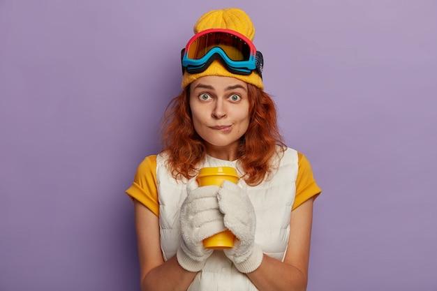 매력적인 여성 모델의 사진에는 생강 머리카락이 있고 입술을 물고 양손으로 테이크 아웃 컵을 들고 카메라를 직접 바라보고 조끼가 달린 노란색 티셔츠를 입습니다. 무료 사진
