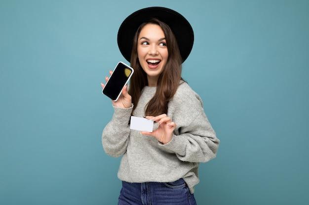 黒い帽子と灰色のセーターを着ている魅力的な楽しい若いブルネットの女性の写真 Premium写真