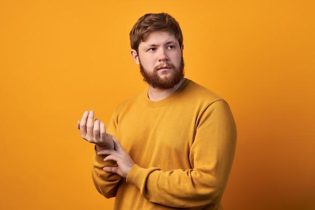 매력적인 남자의 사진은 둥근 안경을 착용하고 손목에 손을 대고 맥박 또는 심박수를 확인하고 건강을 돌보고 심장 두근 두근을하고 흰색 배경에 모델을합니다. 프리미엄 사진