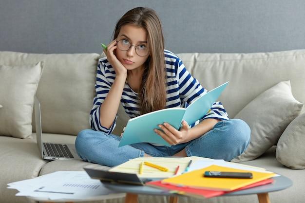 魅力的な女性の写真は、記事を書き、スタートアッププロジェクトを開発し、快適さを楽しみ、ラップトップコンピューターを備えたソファのリビングルームでポーズをとり、足を組んで座り、丸い眼鏡をかけ、真面目な顔つきをしています 無料写真
