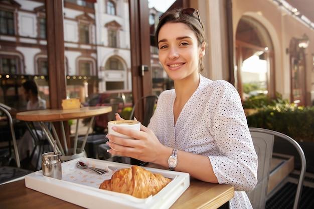 그녀의 머리에 선글라스와 함께 매력적인 젊은 갈색 머리 여자의 사진, 여름 테라스에서 아침을 먹고 제기 손에 커피 한잔을 유지하고 널리 미소 무료 사진