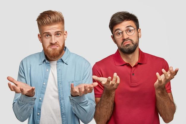 あごひげを生やした躊躇している男性の写真は、無知な表情をしていて、チームとして一緒に働いて、プロジェクトを成功させる方法がわからず、ファッショナブルな服と丸い眼鏡をかけ、賢くて勤勉です 無料写真