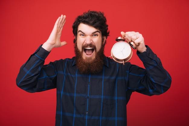 残り時間を心配して、ビンテージの時計を保持しているひげを生やした男の写真。時間管理と規律。 Premium写真
