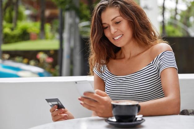 美しい女性観光客の写真は現代の電話とクレジットカードを使用してオンラインでチケットを予約します。 無料写真