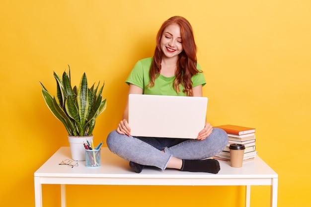 Фотография красивой молодой рыжеволосой студентки колледжа, сидящей на белом столе с топом на коленях, небрежно одетой, работающей онлайн или обучающейся дистанционно. Бесплатные Фотографии