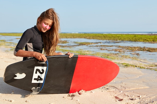 初心者の女性サーファーがボードを修理しようとしている写真、黒いウェットスーツを着て、顔に亜鉛サーフマスクがあります 無料写真