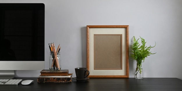검은 빈 화면 컴퓨터 모니터, 책, 노트북, 연필 홀더, 액자, 화분 흰색 시멘트 벽에 함께 넣어 함께 검은 책상의 사진. 프리미엄 사진