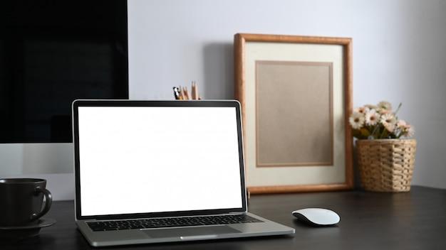흰색 빈 화면 컴퓨터 노트북, 책, 노트북, 연필 홀더, 액자, 화분 흰색 시멘트 벽에 함께 넣어 함께 검은 책상의 사진. 프리미엄 사진