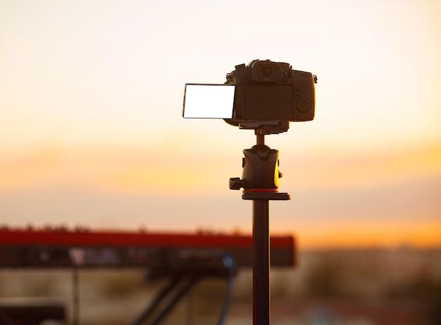 屋外でのライブコンサートを撮影する空の空白の画面を持つカメラの写真 Premium写真