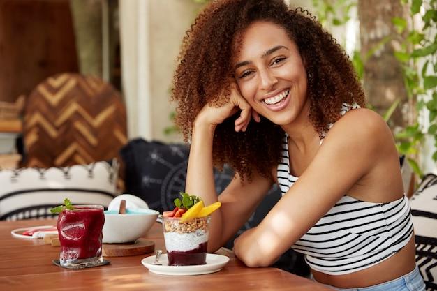 屈託のない混血女子大生が大学で疲れた一日を過ごし、難しい試験に合格した後の休息、美味しいデザートを食べ、結果に満足して温かい前向きな笑顔を示している写真 無料写真