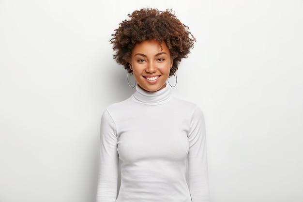 巻き毛のカリスマ的な素敵な女性の写真は、顔に楽しい、歯を見せる笑顔を持っています 無料写真