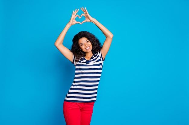 당신에게 심장 기호를 보여주는 웃 고 명랑 긍정적 인 좋은 여자의 사진 프리미엄 사진