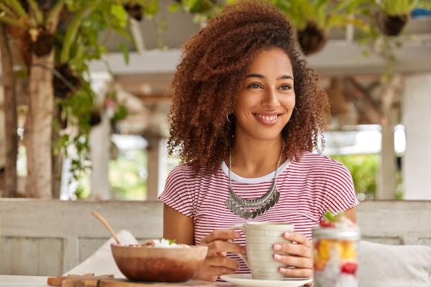 巻き毛の陽気なリラックスした黒人の女の子の写真、コーヒーのマグカップを保持し、娯楽を楽しんで、エキゾチックなカフェテリアを訪問し、海外で夏休みを過ごし、脇を見る 無料写真